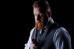 Man smoking a pipe. Portrait of a red bearded man smoking a pipe on black background Stock Photos