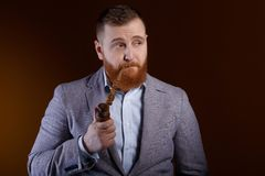 Man smoking a pipe. Portrait of a red bearded man smoking a pipe on a brown background Royalty Free Stock Photography