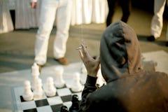 Man smoking, playing shess Royalty Free Stock Images