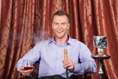 Man smoking shisha in restaurant and drinking. Stock Photos