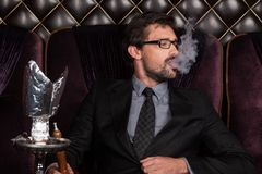 Man smoking shisha in restaurant. Stock Photography