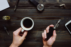 Man smoking vape or electronic cigarette and drinking coffee. View from above. Hipster or bussinesman style. Royalty Free Stock Photography