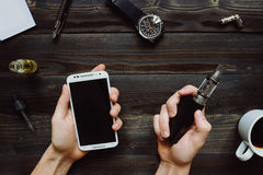 Man smoking vape or electronic cigarette and using smartphone. View from above. Hipster or bussinesman style. Royalty Free Stock Photo