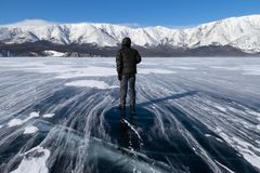 A man on smooth surface of frozen mountain lake during a strong. A man standing on beautiful smooth surface of frozen mountain lake during a strong wind in stock photos