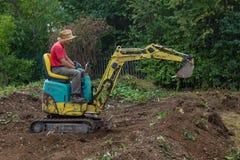 Man smoothing terrain with a mini digger. Man smoothing the terrain with a mini digger Royalty Free Stock Photos