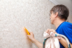Man smoothing the wallpaper with a spatula Stock Photo