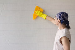 Man smoothing wallpaper with spatula Royalty Free Stock Photos
