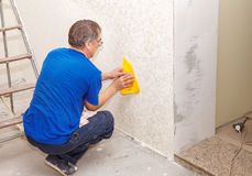 Man smoothing the wallpaper with a spatula Stock Photos