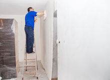 Man smoothing the wallpaper on the wall Stock Images