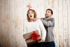 Man smothering girl holding christmas gift over wooden background. Stock Photo