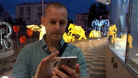 Man sms texting using app on smart phone at night in city. Handsome young business man using smartphone smiling happy. Wearing suit shirt outdoors. Urban male stock footage
