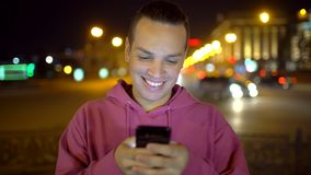 Attractive hispanic man with a beautiful smile using mobile phone. Man sms texting using app on smart phone at night in. Man sms texting using app on smart phone stock footage