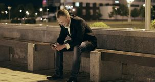 Man sms texting using app on smart phone at night in city. stock video