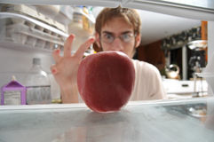 Man snatching apple from fridge Royalty Free Stock Photography