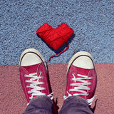 Man in sneakers and heart-shaped coil of yarn on the asphalt Stock Images