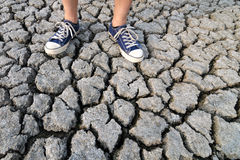 Man in sneakers standing on cracked ground during summer drought Stock Photography