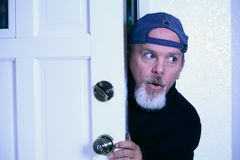 Man sneaking into house from doorway. Stock Photo