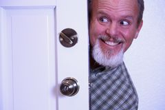 Man sneaking into house from doorway. Stock Photos
