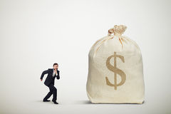 Man sneaking to the big bag of money Royalty Free Stock Photos