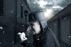 Man sneezing in handkerchief in front of narrow alley in winter. Season Stock Image