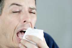 Man Sneezing Into Tissue Stock Image