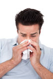 Man Sneezing Into A Tissue. Young Man Blowing His Nose In A Tissue Over White Background Stock Image