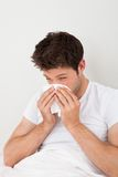 Man Sneezing Into A Tissue Royalty Free Stock Image