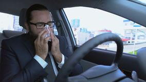 Man sneezing using tissue, suffering allergy while driving car, flu symptom