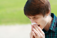 Man sneezing. Young man sneezing outdoor and blowing his nose because he has allergies Royalty Free Stock Photography