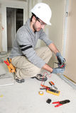 Man snipping wall wiring. Using clippers Royalty Free Stock Photo