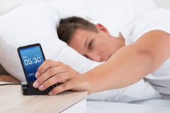 Man Snoozing Alarm Clock On Cell Phone Stock Image