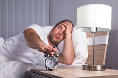 Man snoozing alarm clock Royalty Free Stock Photo