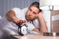 Man snoozing alarm clock Royalty Free Stock Photos