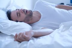 Man snoring because of apnea lying in the bed. Man snoring because of sleep apnea sahs syndrome lying in the bed Stock Photo