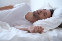 Man snoring because of apnea lying in the bed. Man snoring because of sleep apnea lying in the bed Stock Photo