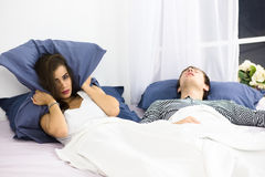 Man snoring in bed. Snoring man. Couple in bed, men snoring and women cannot sleep, covering ears with pillow for snore noise. Caucasian men and women sleeping Stock Photos