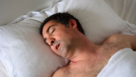 Man snoring in bed. Man in his forties (40s) snoring in bed. Health care concept Royalty Free Stock Photos