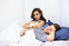 Man snoring in bed. Man sleeping in bed and snoring loudly while his wife sitting near by him and looking at him. Pretty tired lady dreaming about sleeping all Stock Photo
