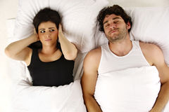 Man snoring keeping woman awake in bed. Beautiful women laid in a white bed awake next to her sleeping snoring boyfriend isolated on a white background Stock Photos
