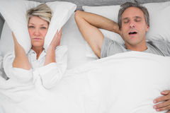 Man snoring loudly as partner blocks her ears. At home in bedroom Royalty Free Stock Image