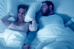 Man snoring and woman can`t sleep, covering ears with pillow for snore noise. Couple in bed, man snoring and woman can`t sleep, covering ears with pillow for Royalty Free Stock Images