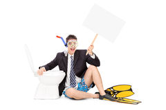 Man with snorkel holding a banner by a toilet Stock Photos