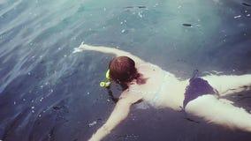 Young woman in bikini snorkeling in mask feeding fish in the sea. slow motion. 1920x1080 stock footage