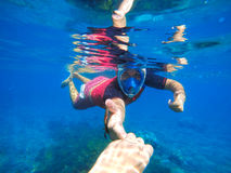 Man snorkeling in mask underwater near the coral reef. Couple holding hands, life underwater near the coral reef, man snorkeling in mask, freediving sport Stock Photos