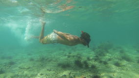 Man snorkelling in tropical waters in slow motion stock video footage