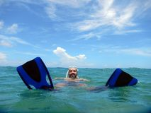 A man snorkling in the ocean. With blue fins and mask Stock Image