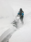 Man Snow Blowing Driveway in Blizzard. Clearing deep snow from driveway with snow thrower in snow storm Royalty Free Stock Photos