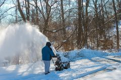 Man snow blowing his driveway. royalty free stock photography