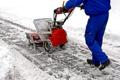 Man and a snow blowing machine Royalty Free Stock Images