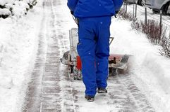 Man and a snow blowing machine Royalty Free Stock Image